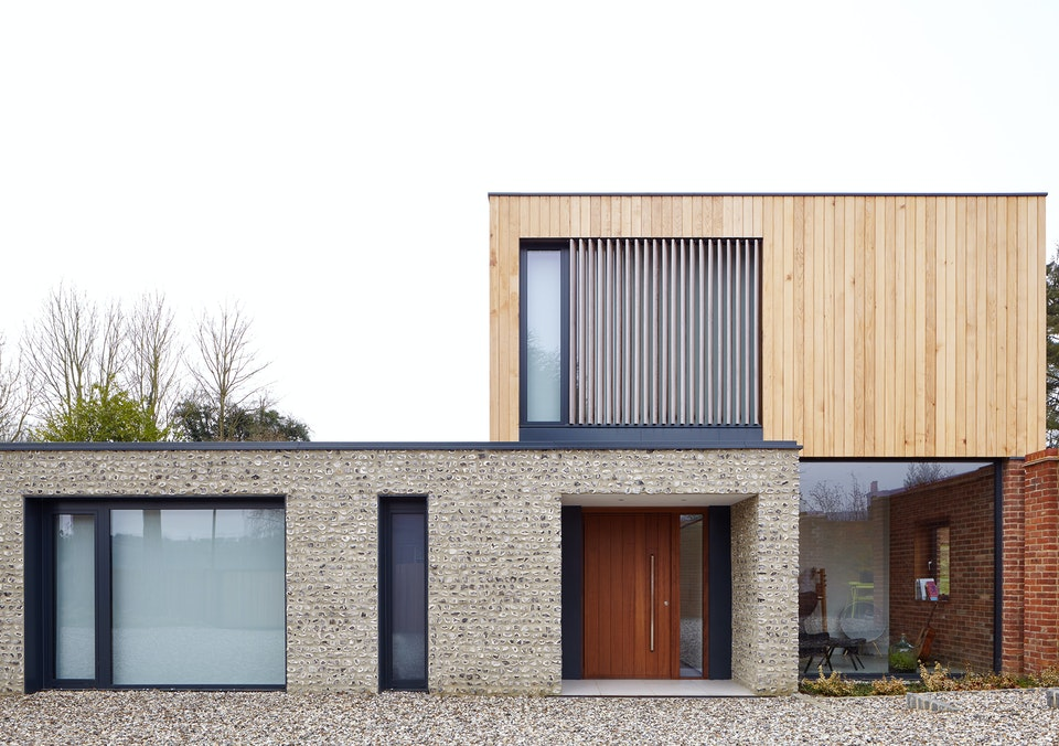 The design of this house with stone and wood cladding lends itself to the bold choice of front door in a stand out oiled Iroko