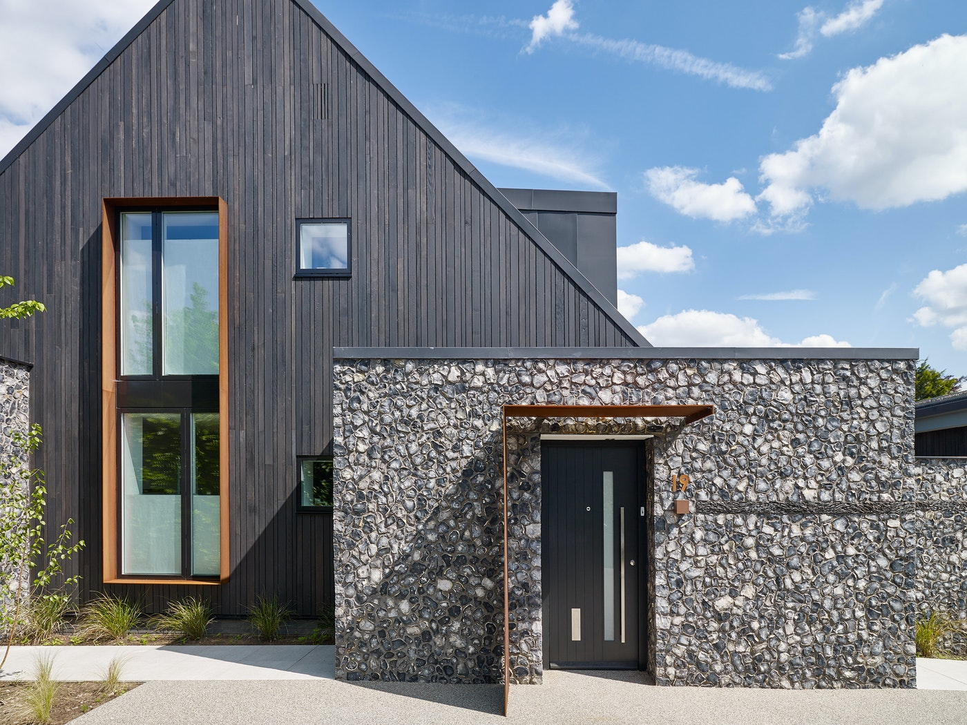Here the door is highlighted by stunning flint work and the rest of the building includes burnt cedar cladding