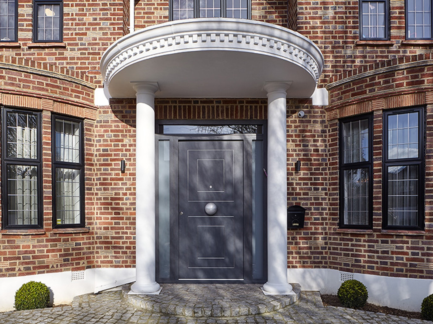 Black windows and a white portico porch make this dark grey door stand out