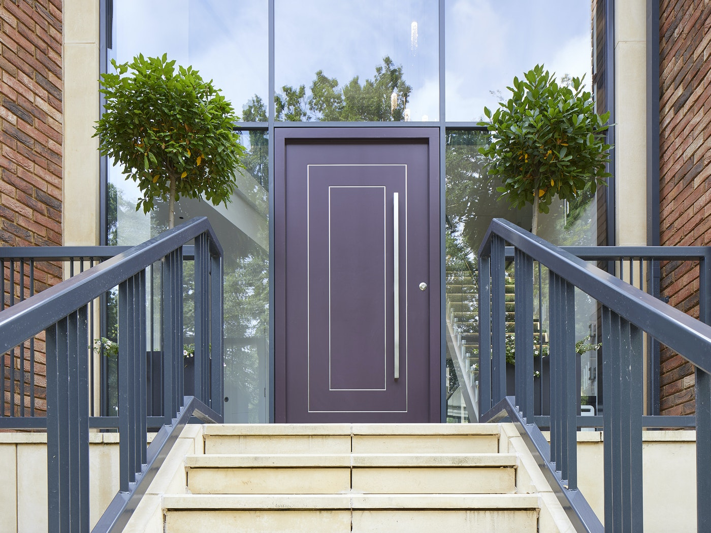 The black aluminium walling, red brick and beige tones of the exterior balance beautifully with the purple door