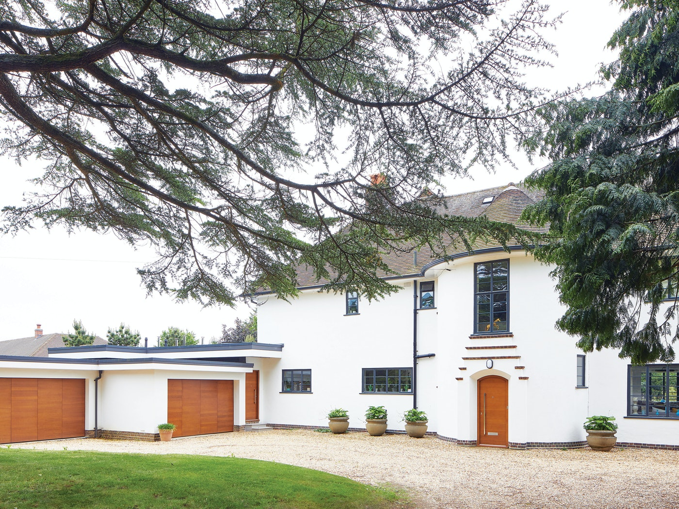 This house errs on the traditional side but is given a contemporary update with its white render and matching iroko front & garage doors in a simple design
