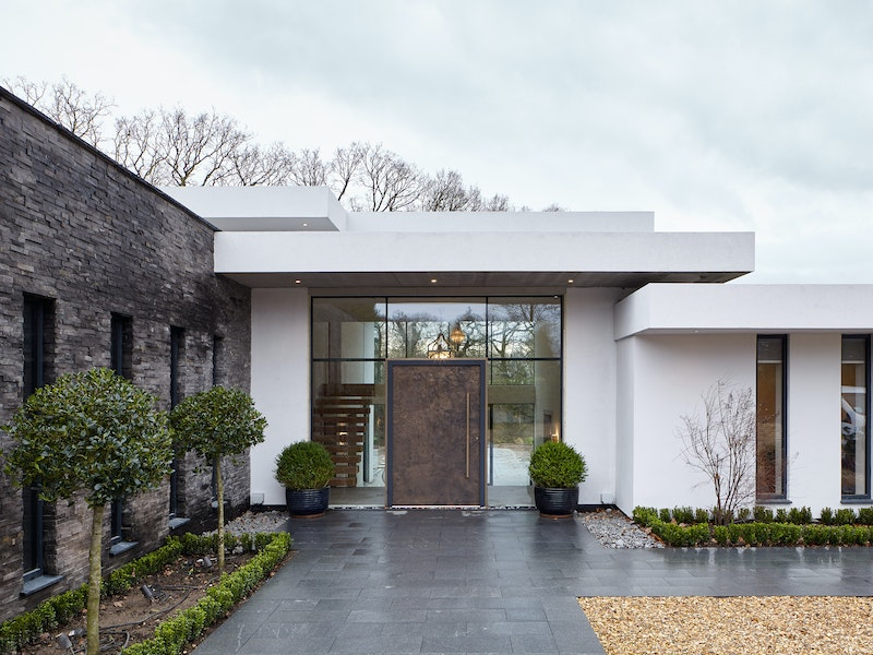 This luxury bronze door brings together the mix of white render, glass walling and grey stonework