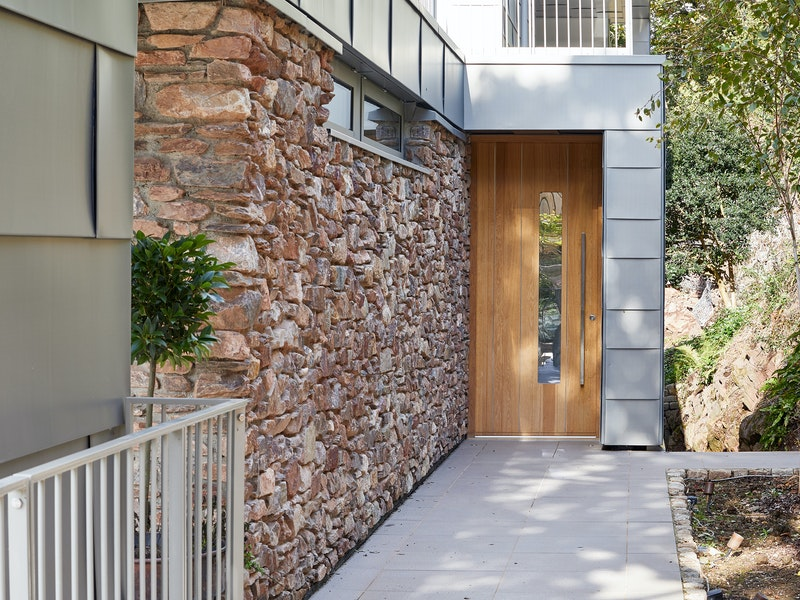europen oak front door with grey cladding and stone wall