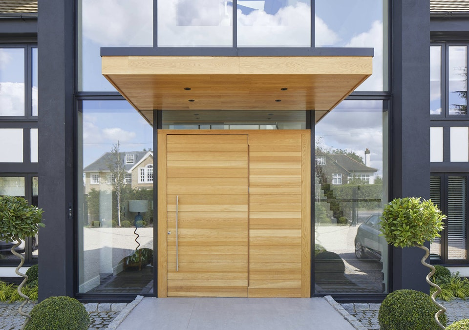 This metal & wooden front door canopy extends a long way in front of this pivot door to give shelter from sun & rain