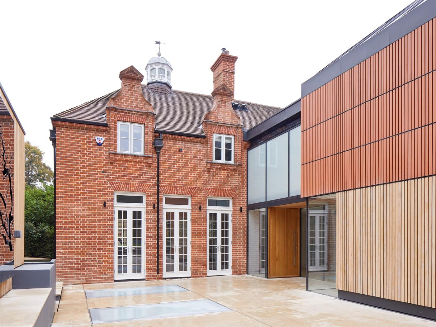 The warmth of the iroko front door works beautifully with the red brick and white windows of this house