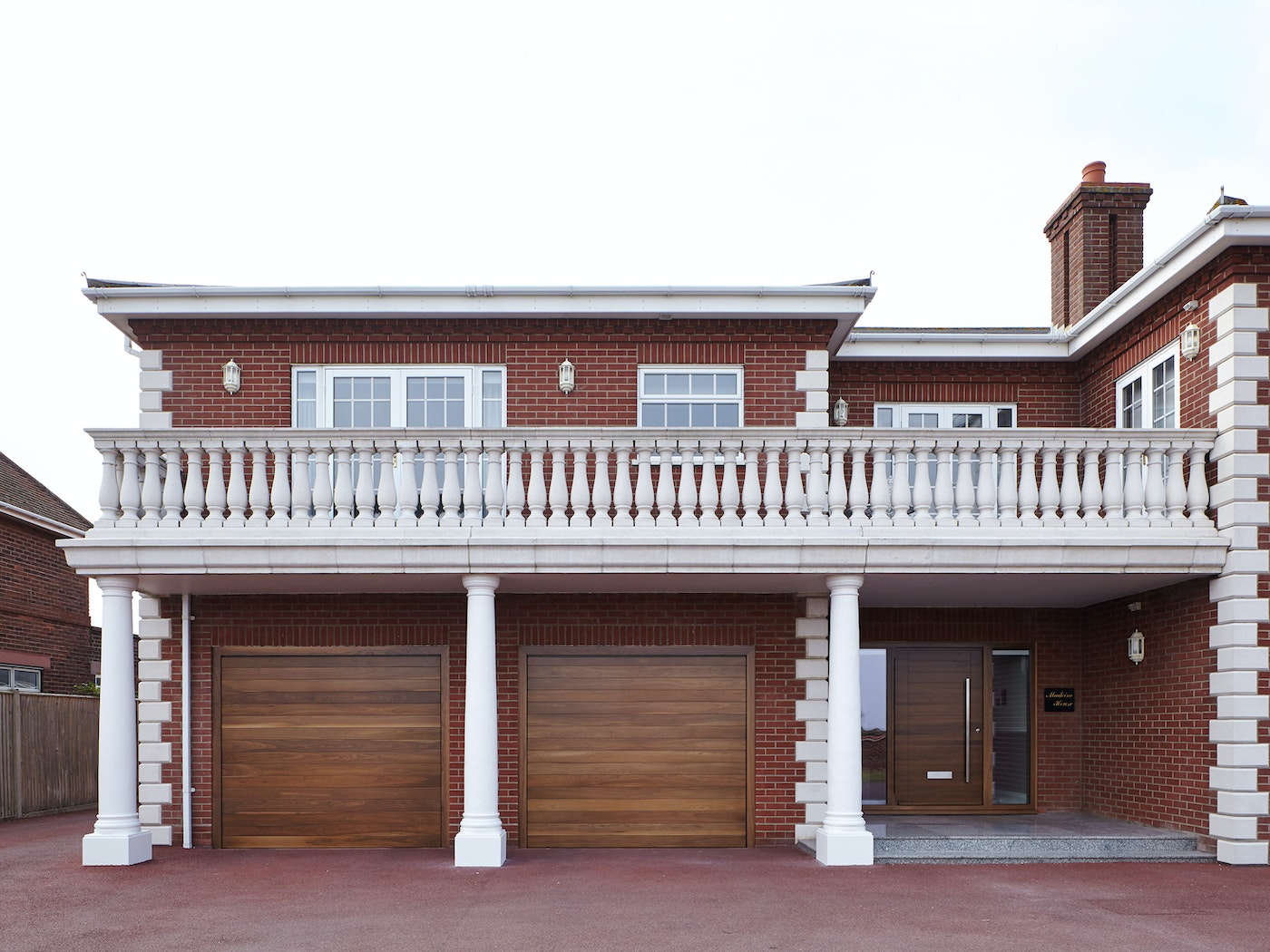 This mixed style new build perfectly blends the warmth of red brick with an Urban Front front door in walnut - along with matching garage doors