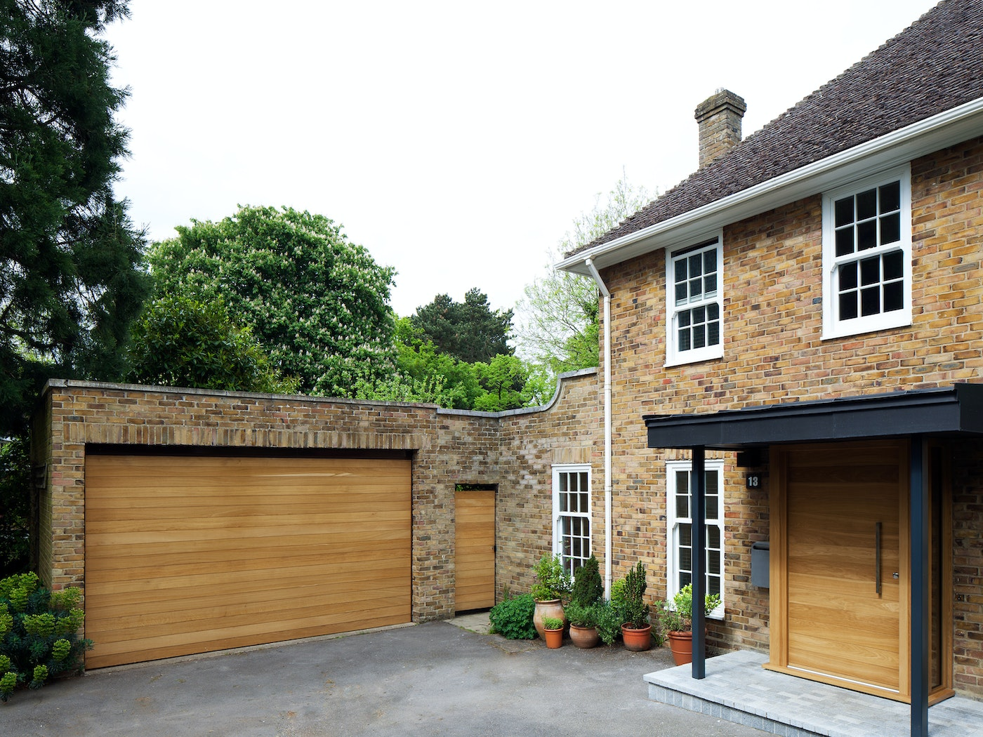 The light beige brick of this house is beautifully offset by matching front and garage doors in a warming european oak
