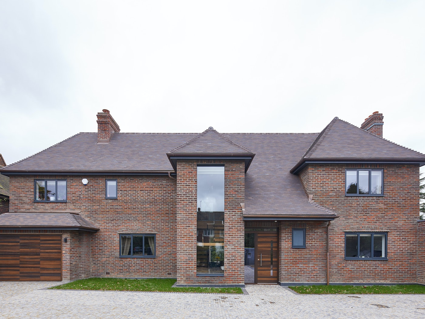 Dark grey windows and the statement glass centrepiece of this brown brick house are tied together with an Urban Front fumed oak front and garage door