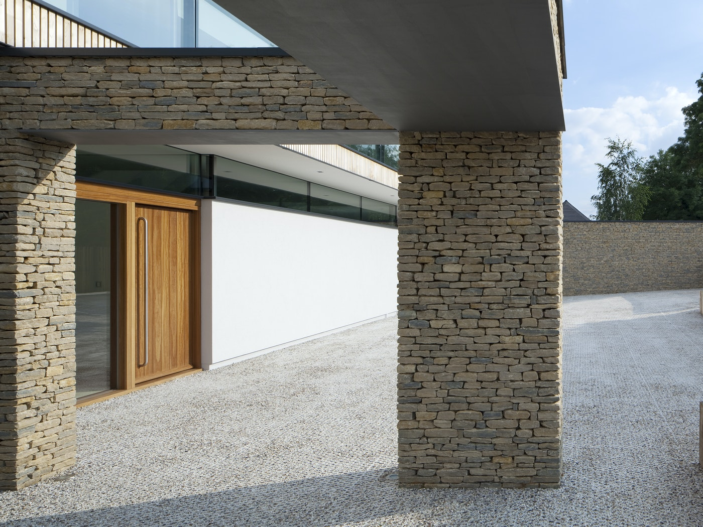 This contemporary house features mixed, light coloured stonework and the iroko front door stands out beautifully