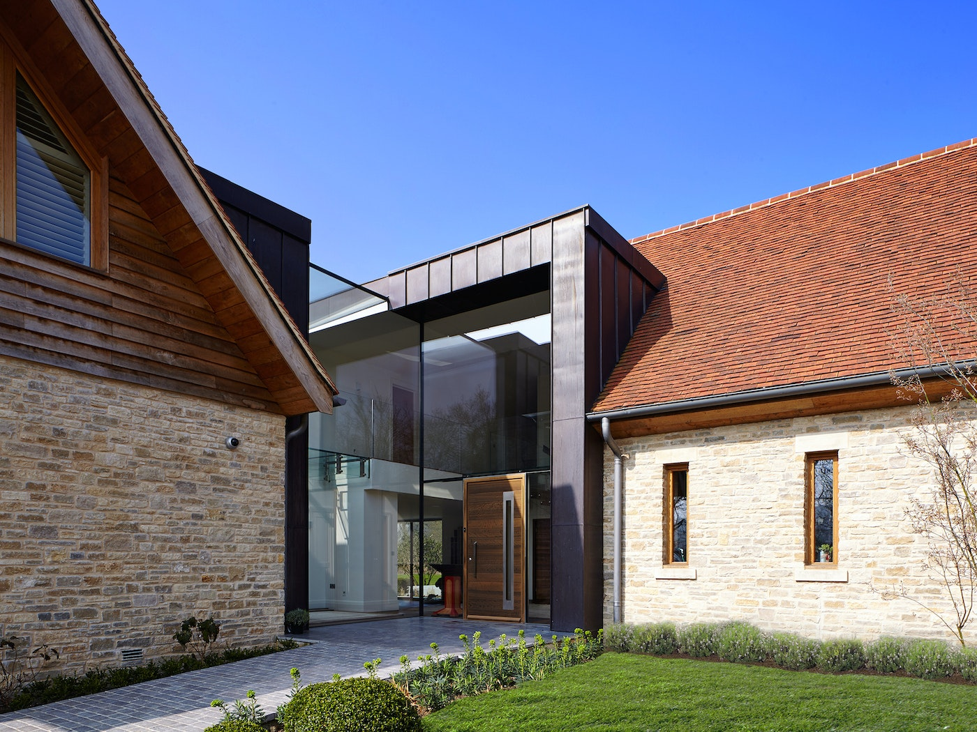 The glass of this facade dominates the entrance way but the fumed oak front door is the standout element bringing the variety of mixed building materials together