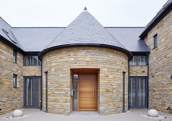 The iroko front door contrasts against the lighter stone in this house