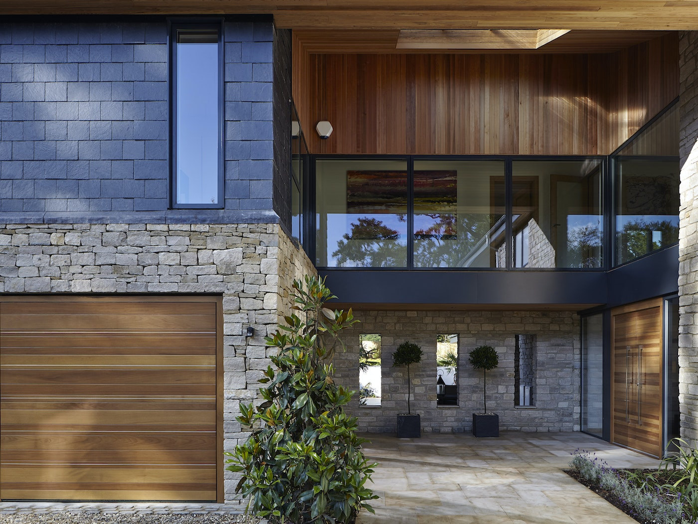 This house features mixed materials but the hardwood front door still works and matches the garage doors and wood cladding