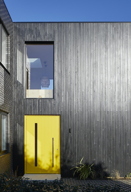 here a striking yellow door really makes a statement against the black cladding