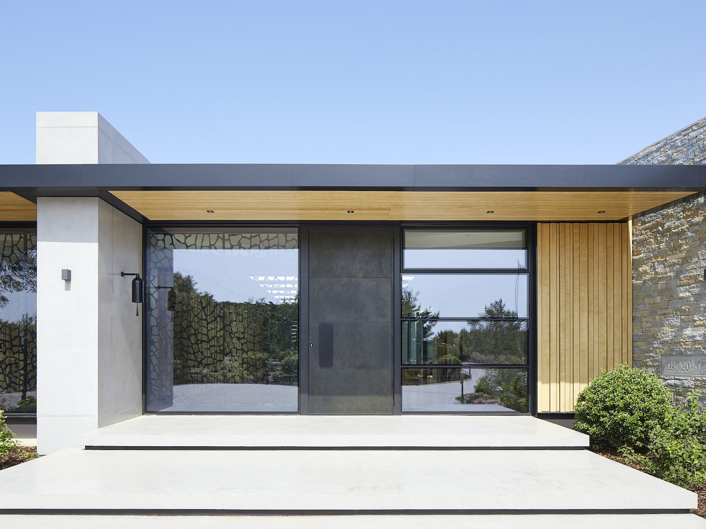 This copper door looks stunning against the architectural glazed wall