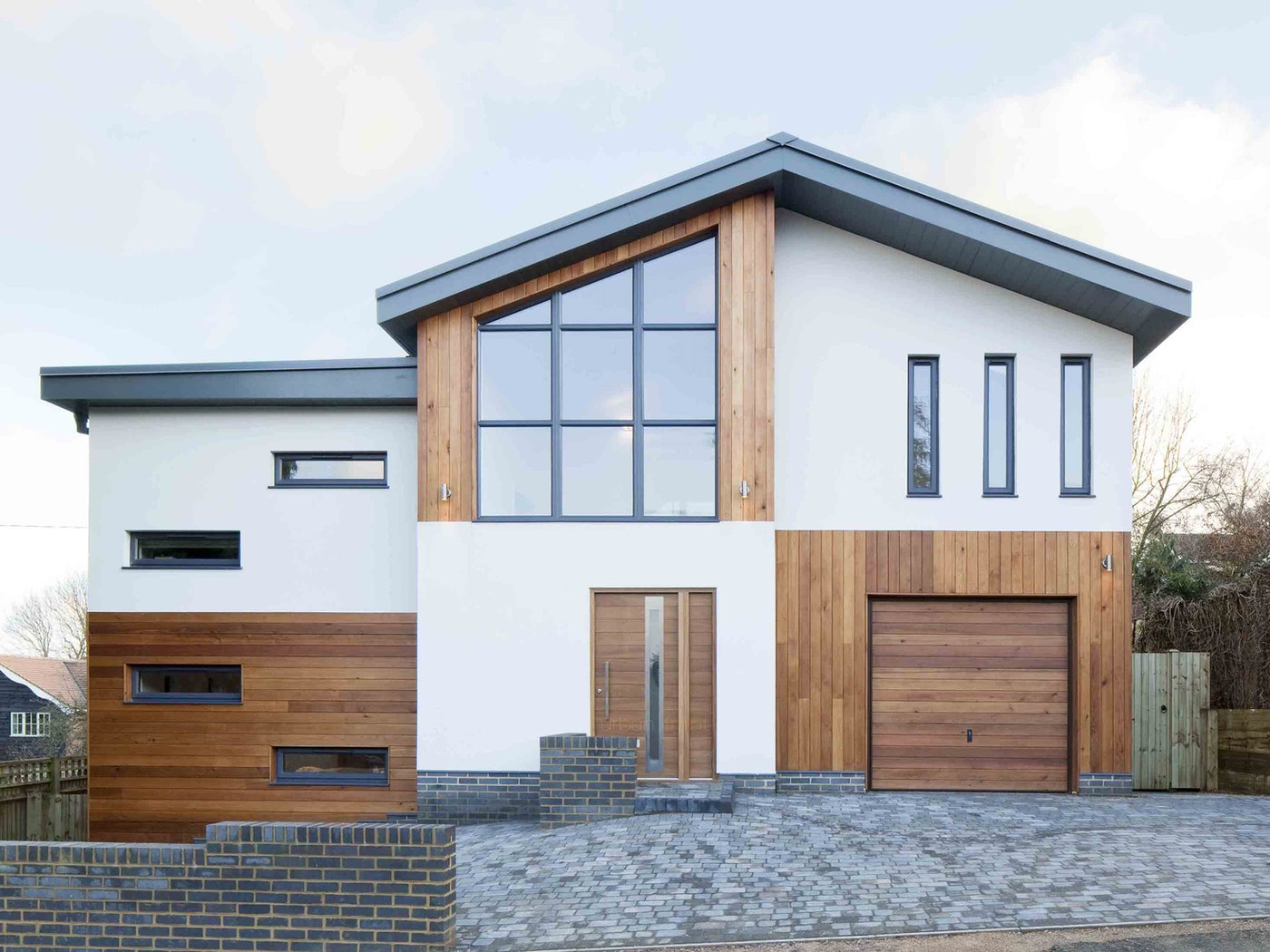 Here the front & garage door designs match, but the glass panel in the front door adds a point of difference and ties in with the contemporary glass styling of the rest of the building