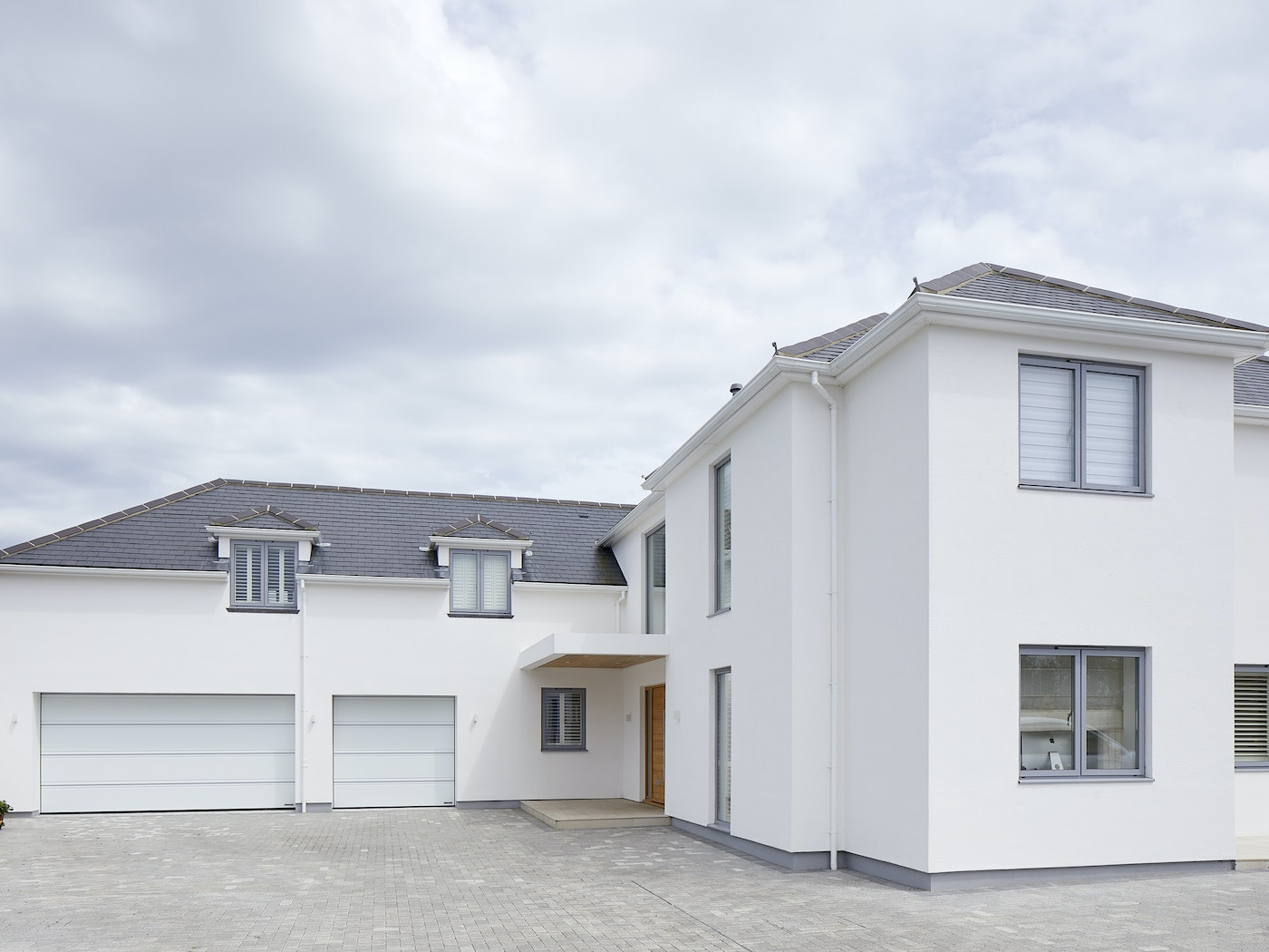 This contemporary house features a minimalist colour scheme, so the owners have chosen to highlight their front door by choosing a natural hardwood finish