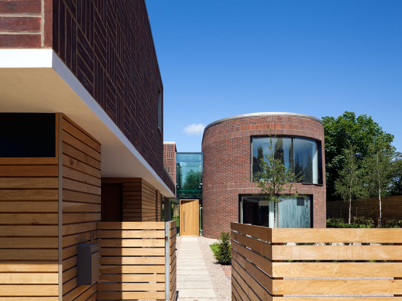 An unusual designed house with circular and square walls with a large door