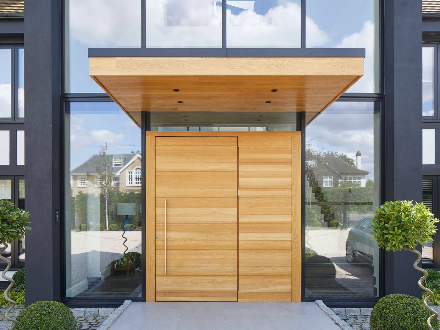 large overhangs will help protect a pivot door from exposure