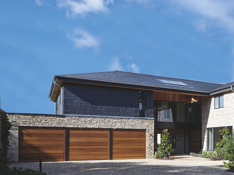 The striking triple garage doors are also iroko wood like the front door