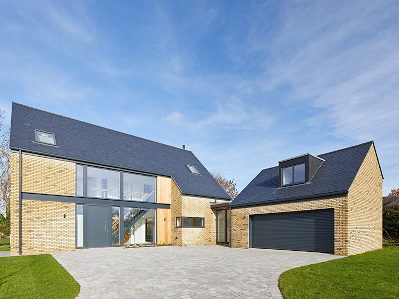 Set into architectural glass, the dark grey front door matches perfectly with the external building materials