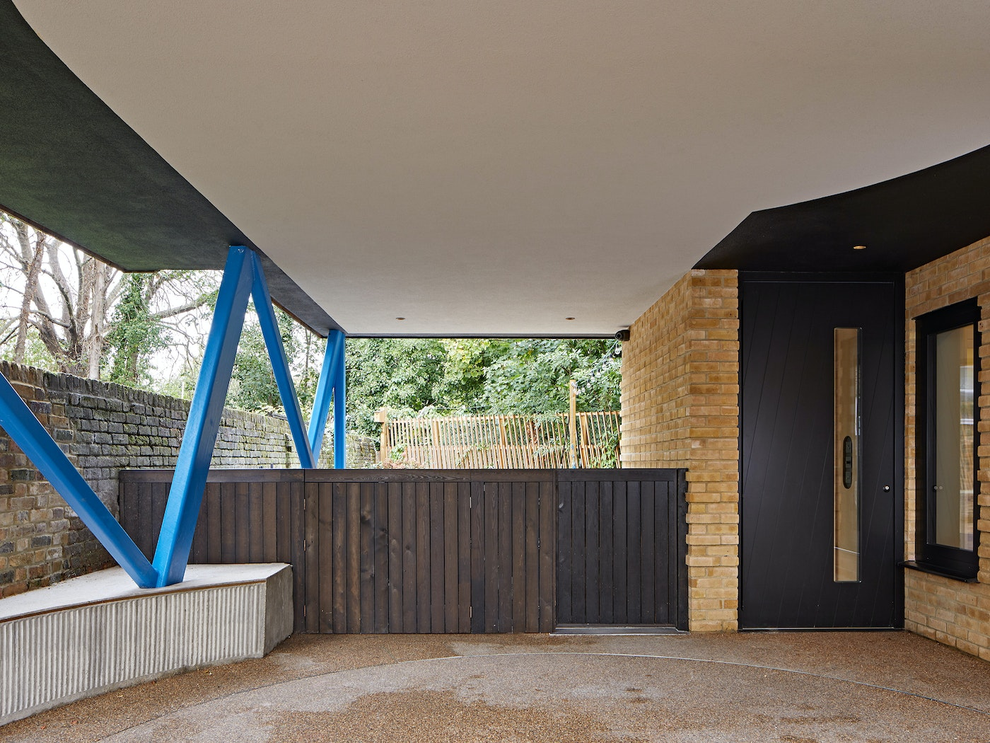 The covered porch space is accented by the attention grabbing blue legs holding the upper level