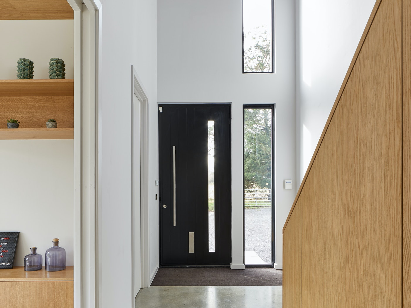 And inside the modern black door sits in a fresh hallway with ample light provided by the door's glass panel & additional windows