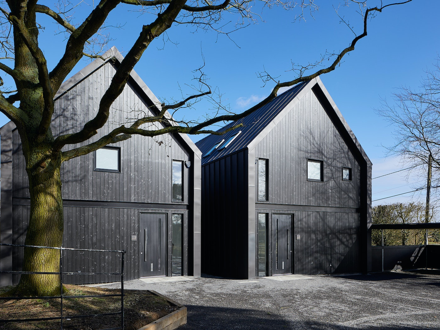 These contemporary houses were designed to mimic farm buildings, complete with black cladding & black exterior doors