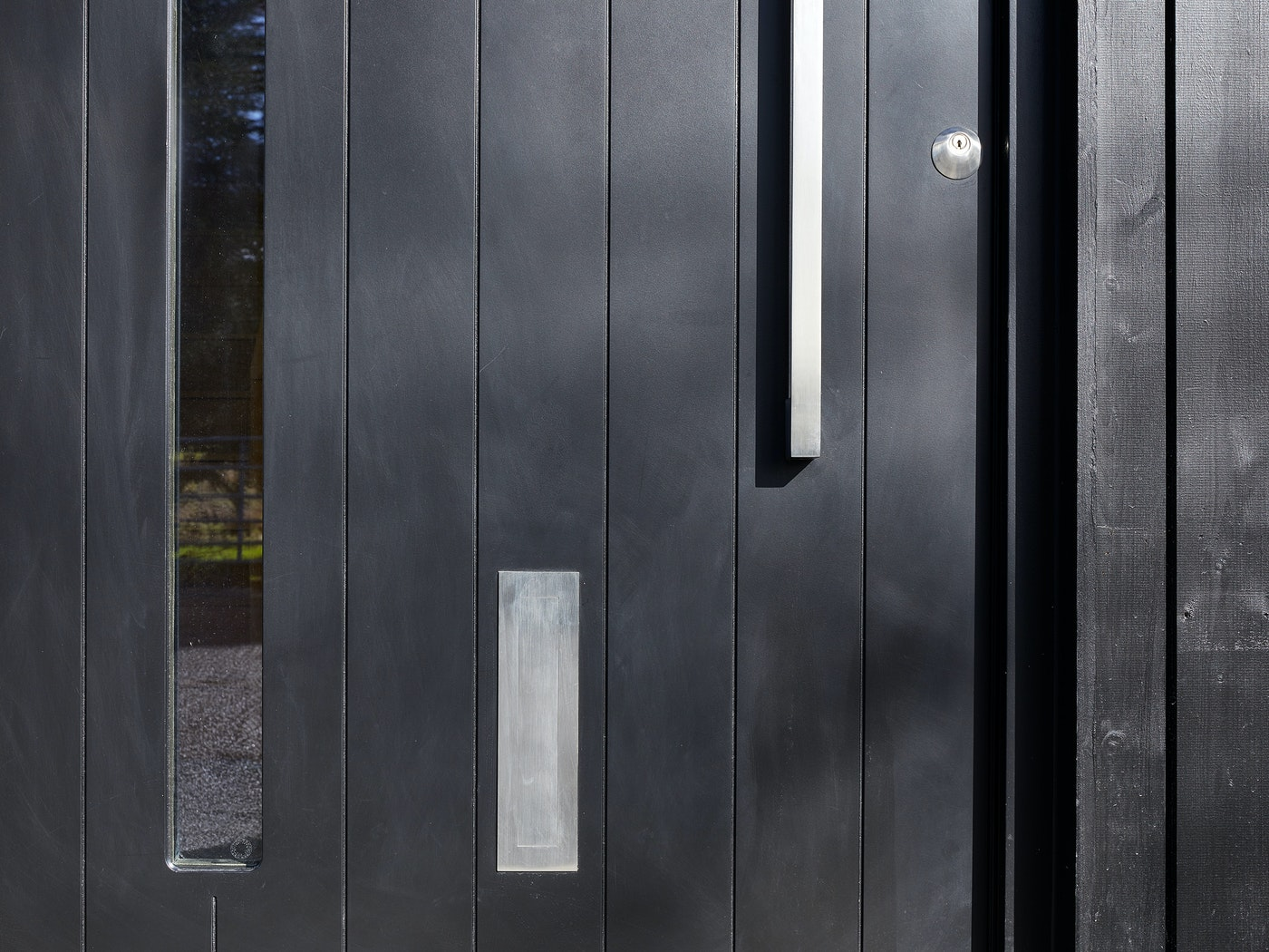This black door design blends seamlessly into the vertical black cladding