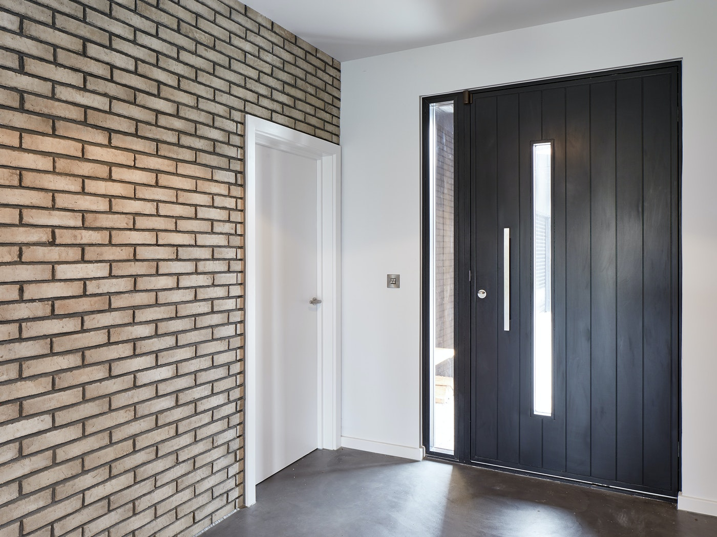 The brick wall & bright white paint nicely highlights the contemporary black door in this hallway