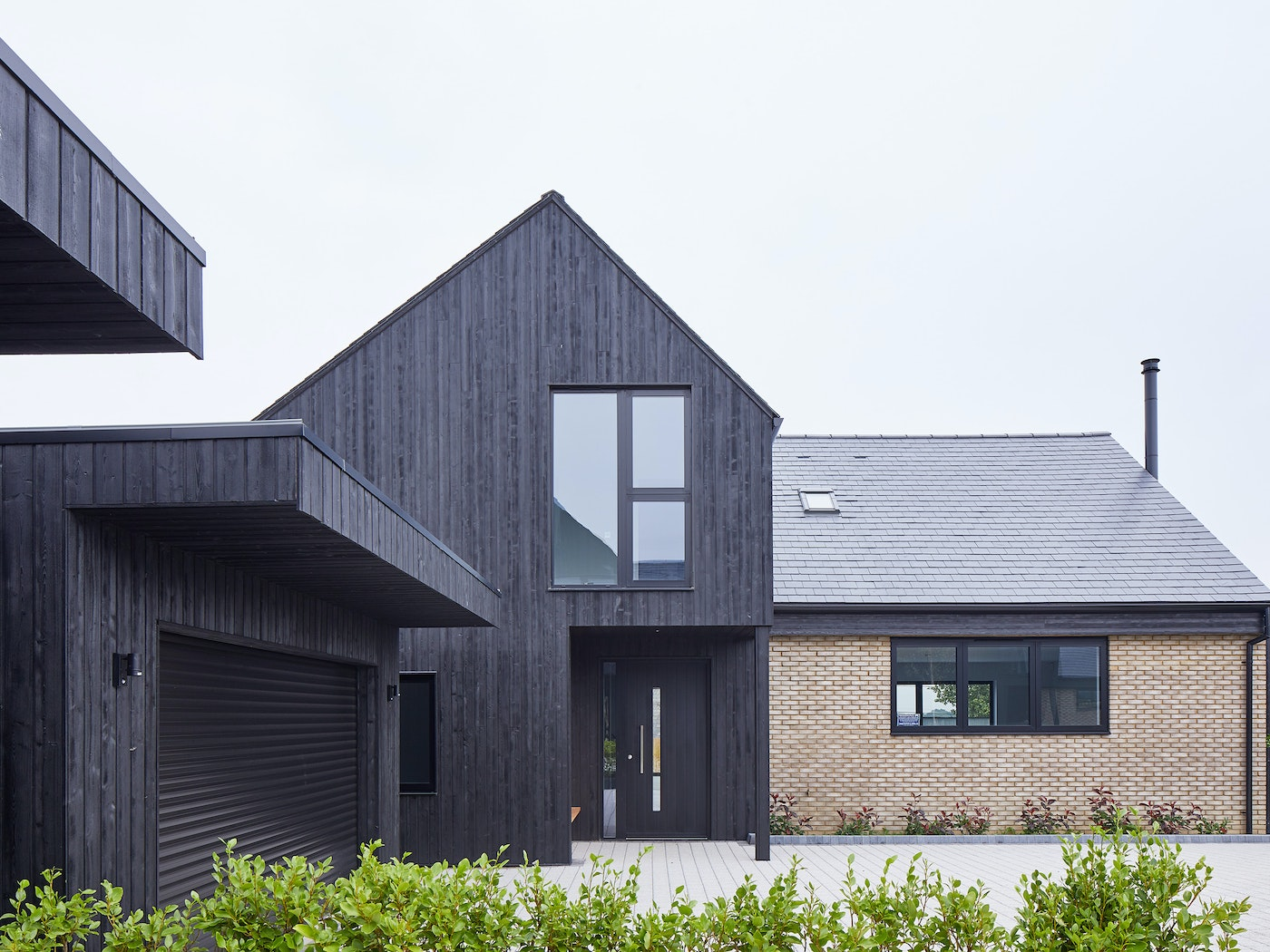 Urban Front's black painted Terano doorsets work well with the charred cladding in this development