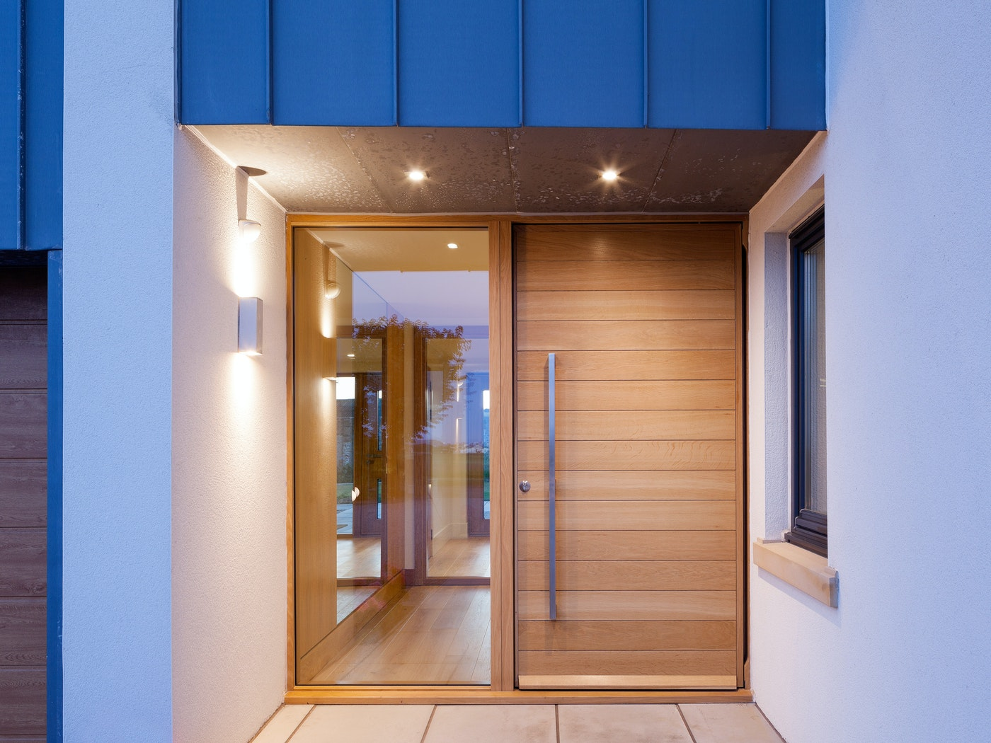 The Parma front door has a glass side panel that complements the glass design in the house