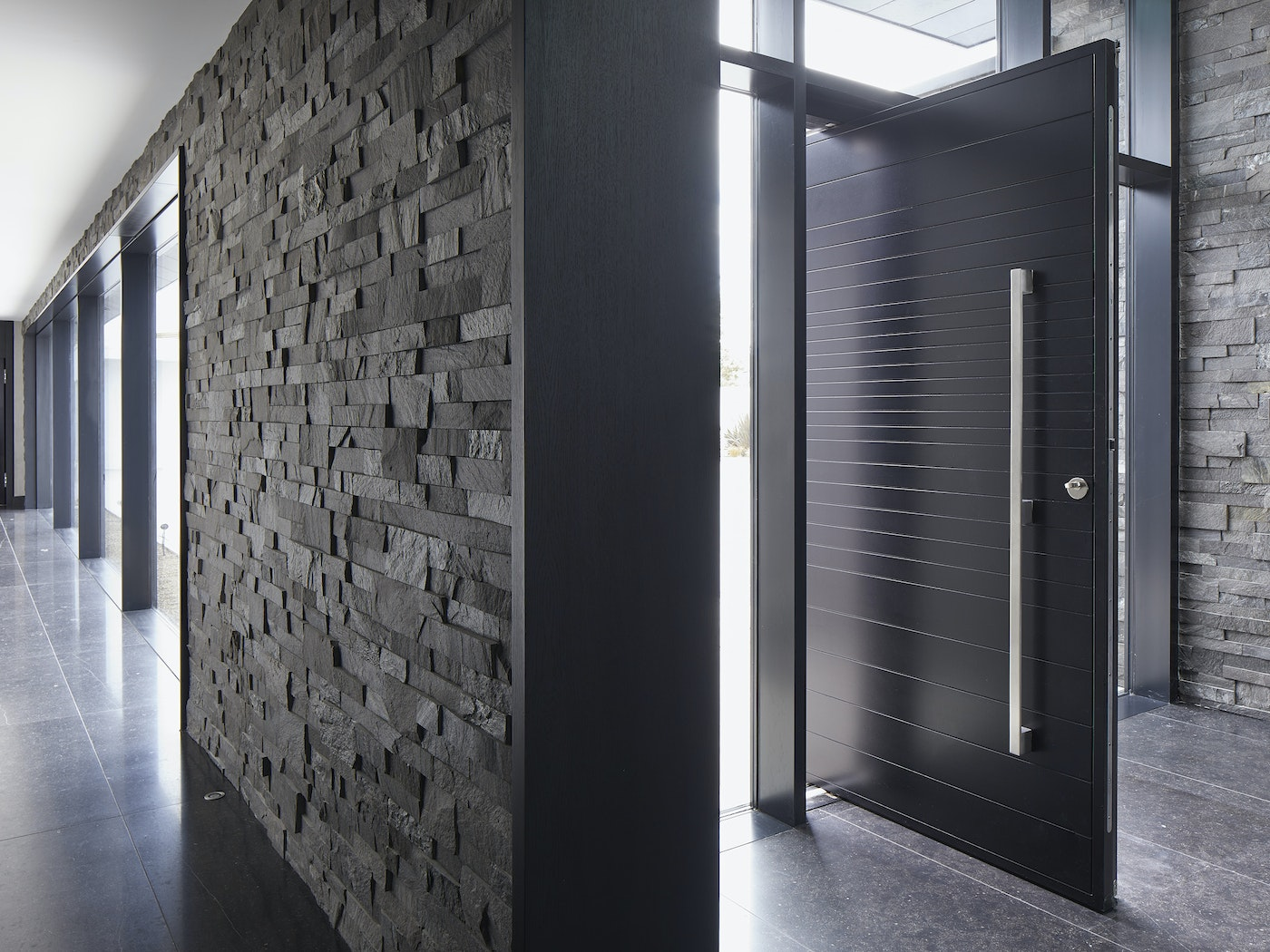 This Neo pivot doorset sits well with the dark tiled floor and the dark grey stone cladding