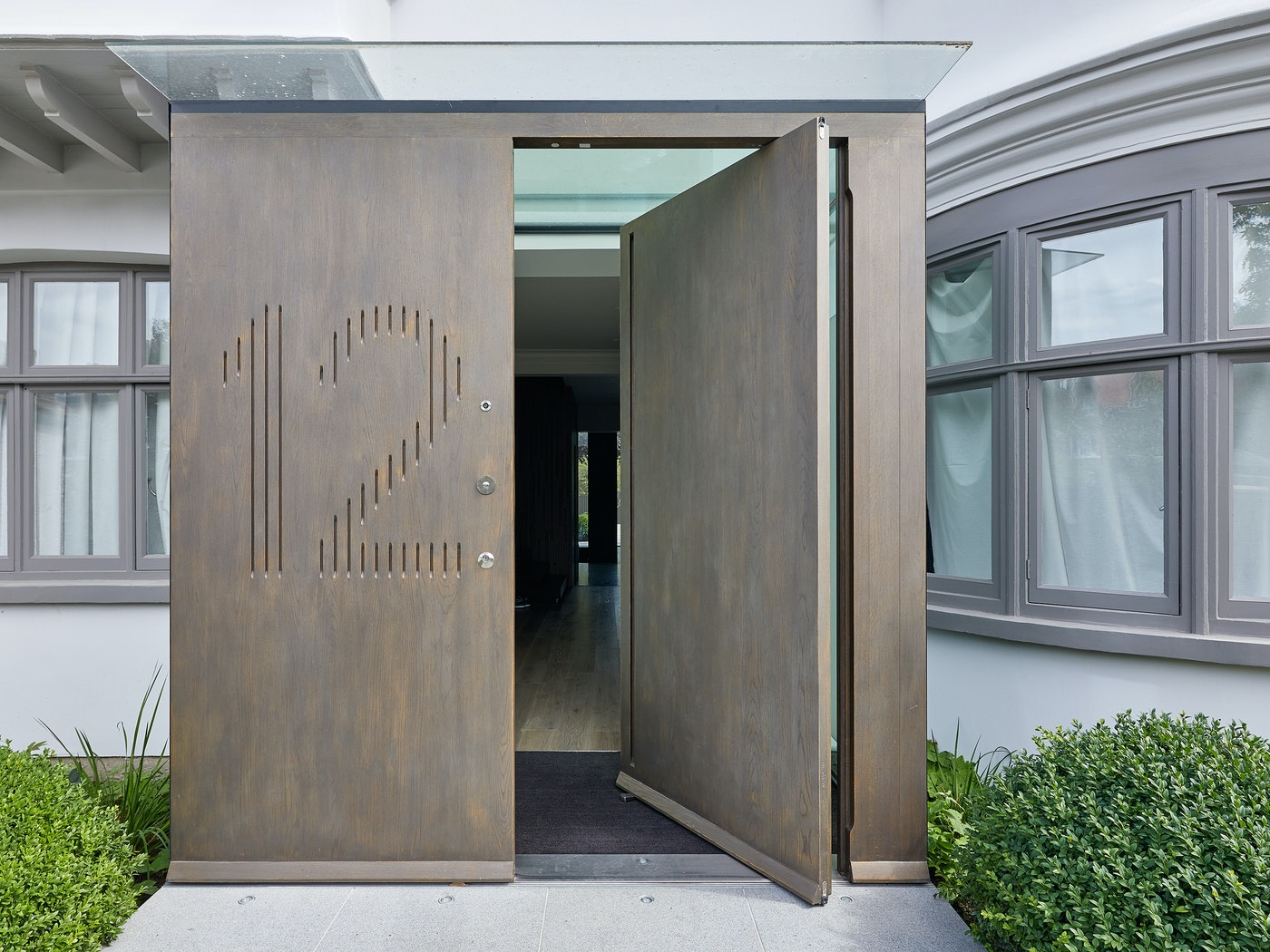 Raw E80 pivot door set with matching boarded panel with number engraving in European stained Onyx metallic finish