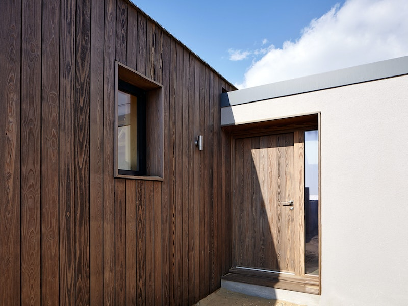 The contemporary Porto front door matches the exterior cladding