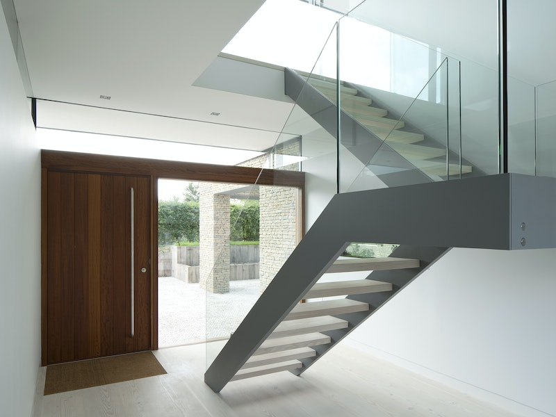 The minimalist interior is made even more impressive with the contrasting front door and staircase