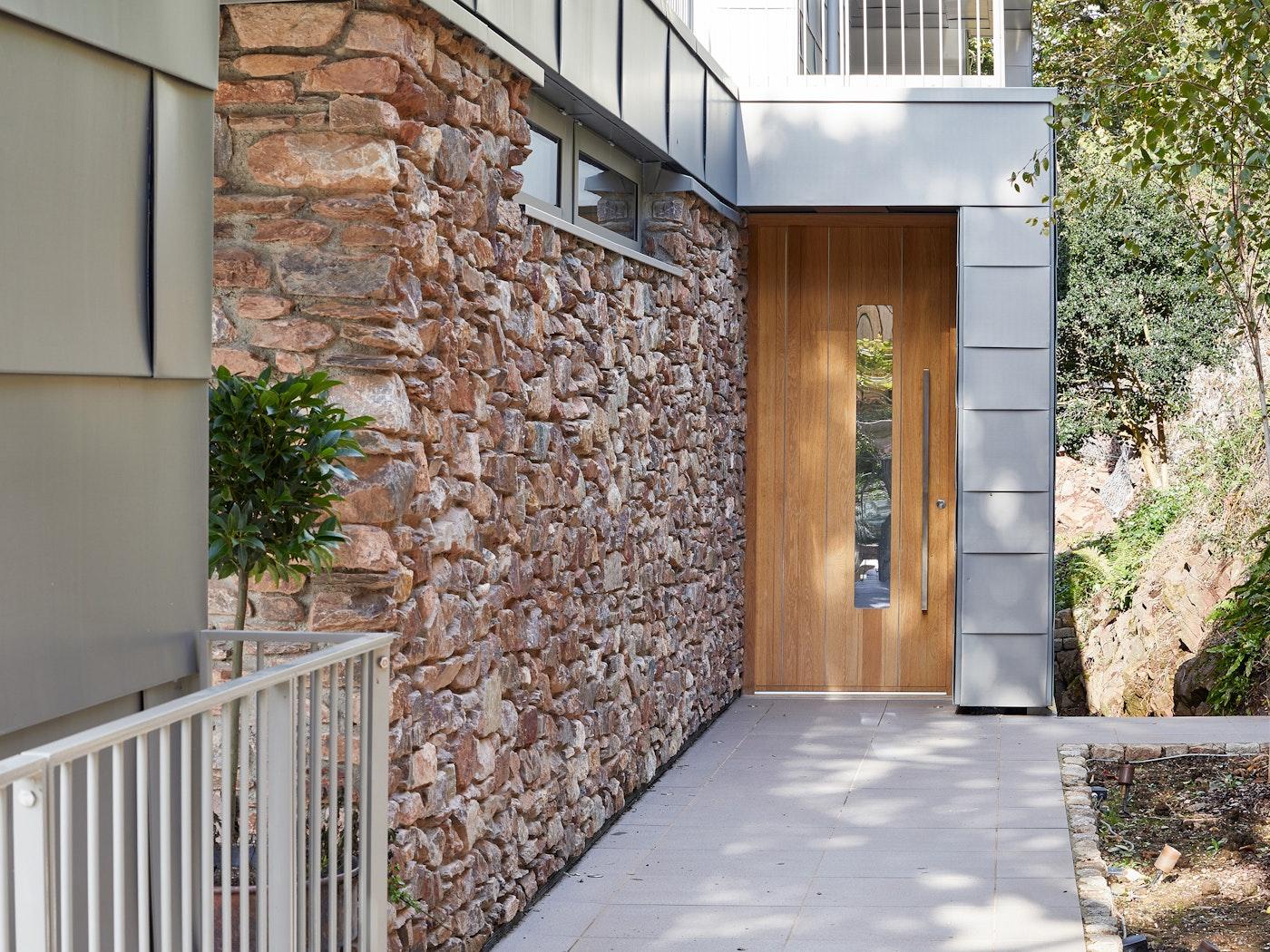 The Urban Front europan oak front door is framed by stone & zinc