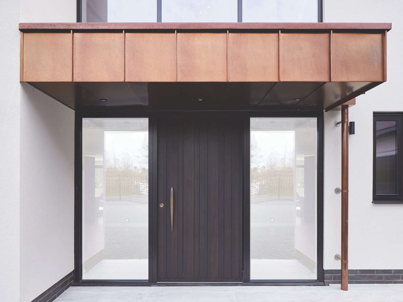 Rondo V in Fumed Oak with painted RAL side lites which work very well with the copper overhang/ entry detail