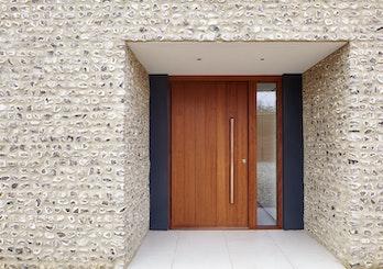 The iroko door is framed by dark grey & stone