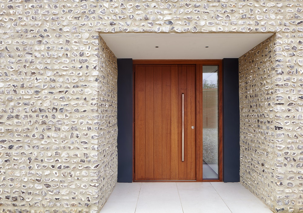 The iroko door is framed by dark grey & stone