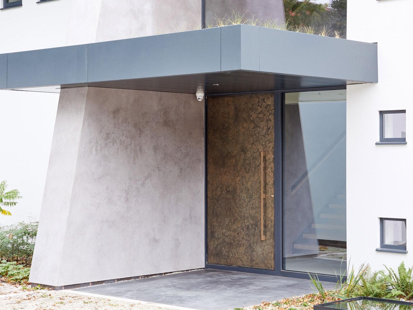 Bronze door against stone exterior | Urban Front