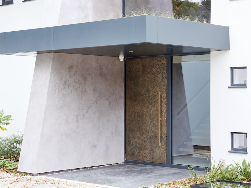 Bronze door against stone exterior | Urban Front