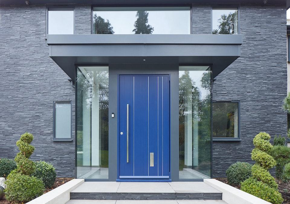 Frameless glass houses this blue door
