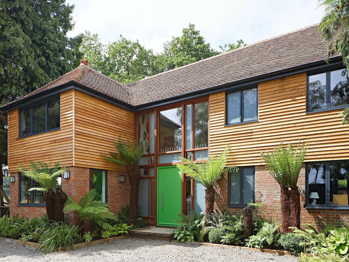 With more neutral cladding and brick tones, this bold green door adds a touch of the tropical to this beautiful property