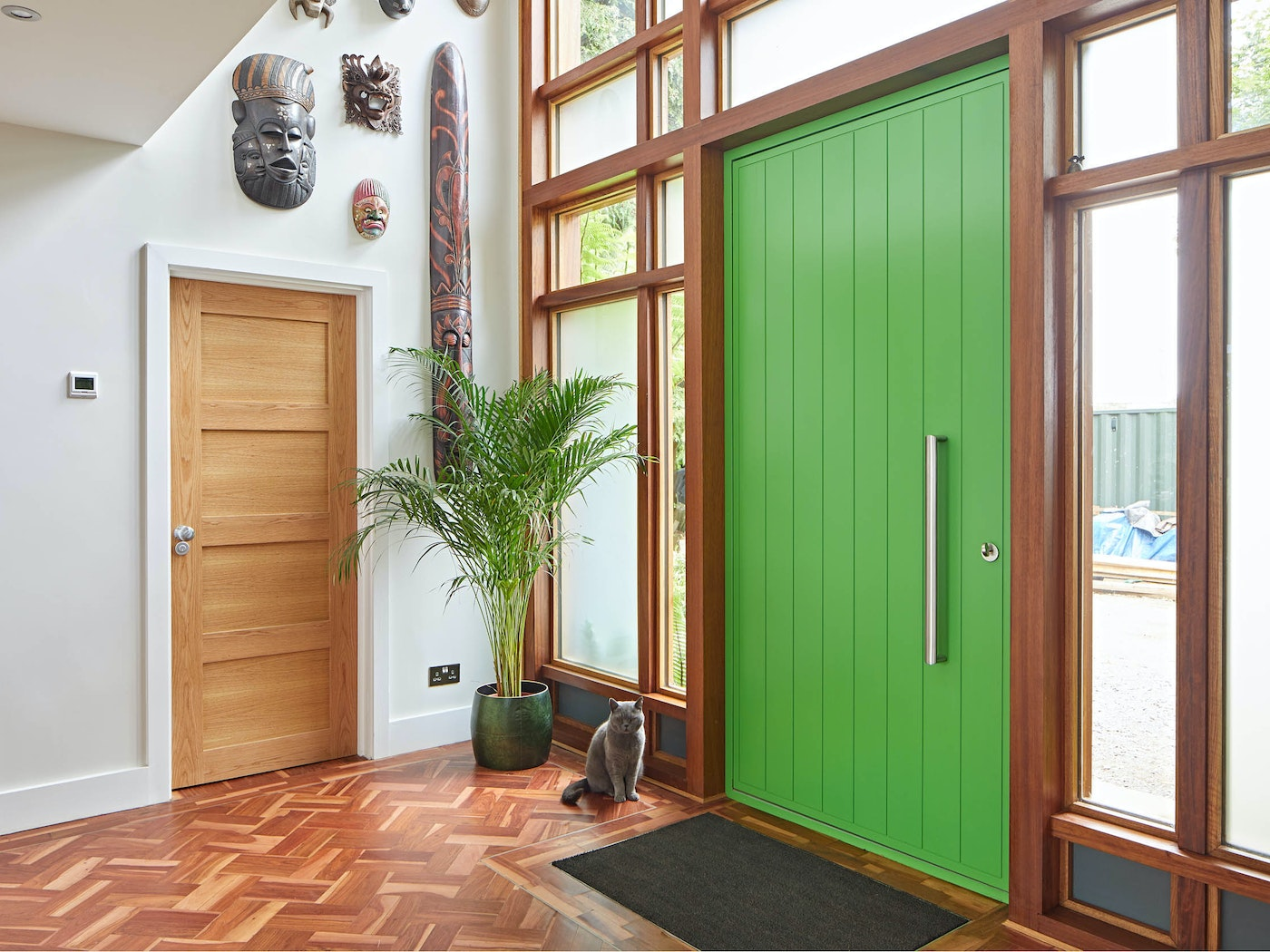 Internally, warm parquet flooring works well with the aluminium curtain frame and nicely contrasts with the vivid green door