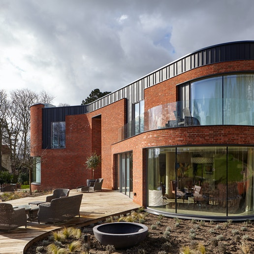 The curved passive house design features 5 Urban Front external doors