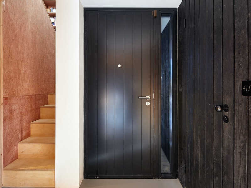 Urban Front's Porto passive front door next to the black cladded wall