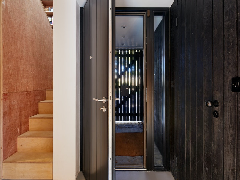 View of front door near the plywood cladded staircase and black cladded wall
