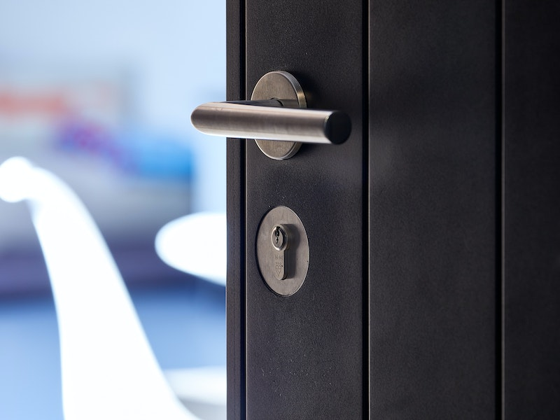 A stainless steel lever handle complements the black painted door