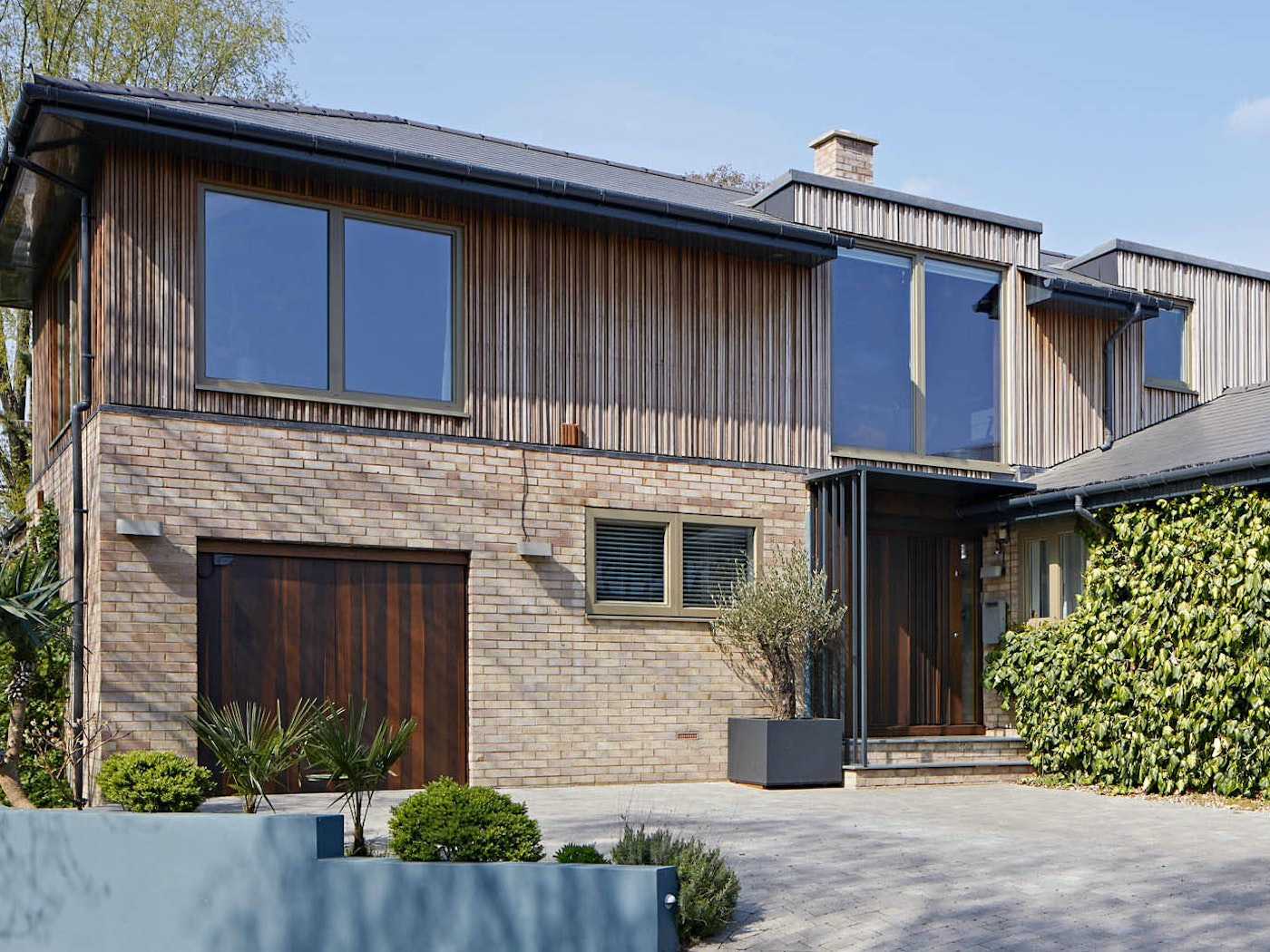 """Complementing the """"Bari"""" on this house is a """"Raw"""" bifold garage door in the same fumed oak wood. Working together flawlessly with the exterior cladding & brickwork"""