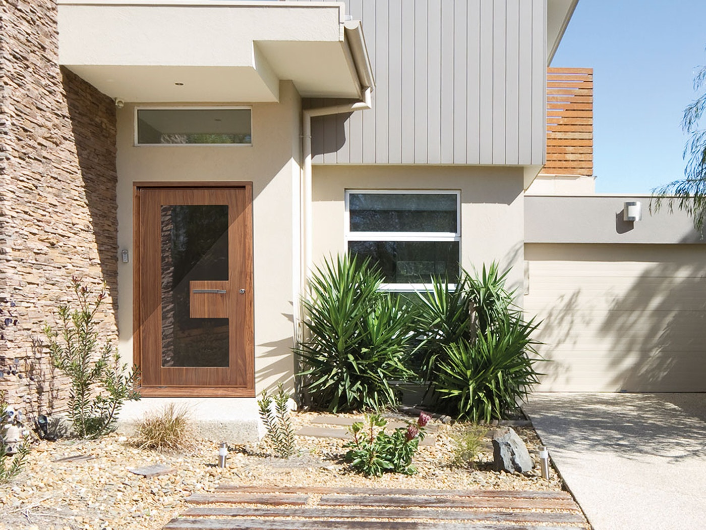 """This """"Ice"""" glazed door in american black walnut lends itself perfectly to the mid-century modern styling of this house"""